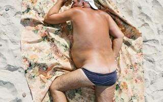 bains-de-soleil-homme-corpulant-echoue-casquette